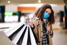 Afro American Woman In Protective Sterile Medical Mask Make Purchases In A Shopping Center, Go Shopping. Spring Shopping. Purchases, Shopping, Lifestyle Concept.