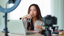 Selective Focus On Camera, Young And Beautiful Asian Girl Holding A Bottle Of Liquid Lotion And Smell It Showing To Camera During Broadcast Video Recording About Cosmetics Content And Review.