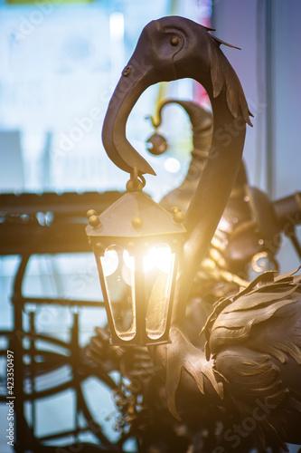 Slika na platnu A metal flamingo holds a lantern in its beak. Garden decor