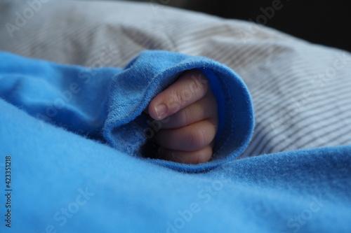 Fototapeta Paluszki noworodka wystający z rękawa obraz