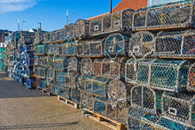 Lobster Pots Stacked Up On A Harbor Quayside