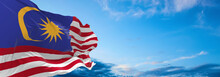 Large Flag Of Malaysia  Waving In The Wind On Flagpole Against The Sky With Clouds On Sunny Day. 3d Illustration