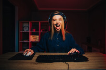 Joyful Woman In A Headset And A Cap On Her Head Plays And Streams Games With A Happy Emotional Face, Looks At The Camera And Shouts Into The Microphone.
