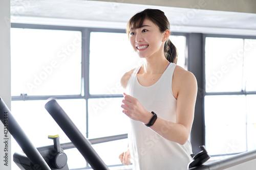 ランニングマシンで走るアジア人女性