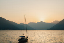 Silhouette Of A Moored Sailing Yacht Against The Background Of The Setting Sun Over The Mountains. Fiery Yellow Sunset Over The Mountains In The Bay Of Kotor In Montenegro.