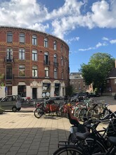A Sunny Day In Amsterdam With Bikes And A Round Vontage Building