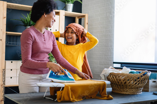 Tela Child helping single parent do household chores and ironing