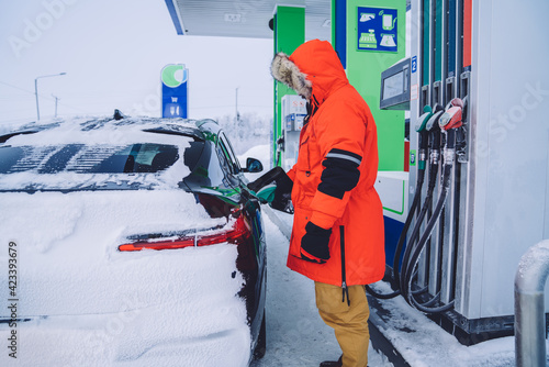Fotografie, Obraz Young male employee of petrol station filling tank of automobile on northern env