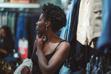 A Beautiful Young Black Woman With A Hanger In Hand Is Pensivelylooking Around While Standing In A Clothing Store With Various Textiles And Clothes Hanging Around; Shallow Depth Of Field