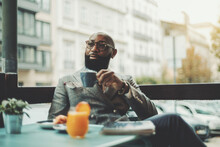 The Portrait Of A Handsome Stylish Wealthy African Guy With A Beautiful Black Beard, In Glasses, Bald, In An Elegant Suit, Sitting On A Rainy Morning In A Street Cafe And Drinking Delicious Coffee