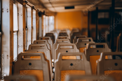 Multiple empty rows of orange seats inside of a passenger boat near the windows; train compartment with plenty of old chairs with handles, selective focus, shallow depth of field