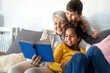 Grandmother studying with multiethnic grandchildren for school