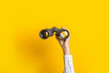 Female Hand Holds Black Binoculars On A Bright Yellow Background