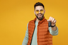 Young Smiling Caucasian Man 20s In Orange Vest Mint Sweatshirt Glasses Giving Car Key Fob Keyless System Look Camera Isolated On Yellow Background Background Studio Portrait. People Lifestyle Concept.