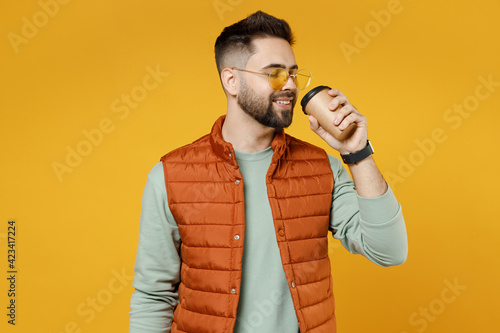 Young smiling cheerful satisfied fun caucasian man 20s wearing orange vest mint green sweatshirt glasses drinking tea hold paper cup of hot coffee isolated on yellow color background studio portrait.