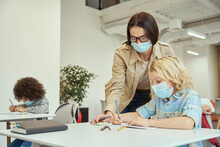 Careful Young Female Teacher Wearing Protective Face Mask Helping Little Boy With The Task. Children Studying In Elementary School, Sitting At The Desk