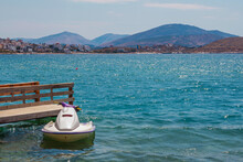 Beautiful Landscape – Summer Resort – Sea Bay With Turquoise Clear Water, Wooden Pier And White Jet Ski, Blue Sky And Mountains On The Horizon. Saranda, Albania.