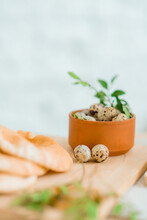 Quail Eggs In A Bowl With Bread And Herbs As An Easter Decor On A Wooden Table In Bright Room.