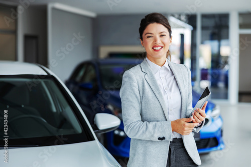Friendly, smiling female car seller standing in car salon and holding tablet while looking at camera.