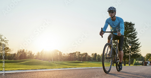 Fototapeta Website header of Rear view of athletic man in sportswear standing with bicycle on the road. Riding mountain road bike on a sunny summer day obraz