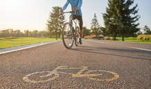 Close Up Of A Bicycle Sign Drawn On Asphalt. Professional Male Cyclist Riding A Road Bike On A Cycle Path In The Background