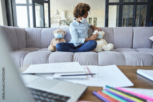 Cute teen schoolgirl child in protective mask putting a mask on her teddy bear toy while sitting on the couch at home during quarantine