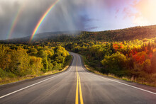 Scenic Highway During A Vibrant Sunny Day In The Fall Season. Dramatic Sunrise Sky With Rainbow Art Render. Taken In Newfoundland, Canada.