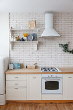 White Classic Kitchen With Brick Wall. Shelf With Grocery Products. Cereals, Pasta And Plates On A White Wooden Shelf. Modern Kitchen Stylish Interior With Cozy Open Shelf, White Gas Stove, Oven