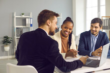 Bank Manager In The Office Consults A Caucasian Man And His African-american Wife. Interracial Couple Takes Out A Loan Or Mortgage To Buy Real Estate. Lending Concept.