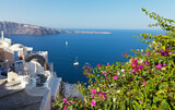 Fototapeta Uliczki - Greece. Santorini island. The beautiful village of Oia with bougainvillea flowers in narrow streets against backdrop of azure waters of the Aegean Sea on sunny day. Seascape. Summer holidays