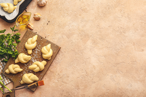 Tela Board with uncooked garlic buns on color background