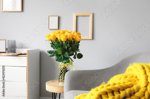 Obraz Vase with beautiful yellow roses on table in interior of room - fototapety do salonu