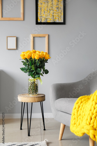 Fototapeta Vase with beautiful yellow roses on table in interior of room obraz