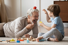 Overjoyed Older Caucasian Grandfather Engaged In Funny Playful Game Activity With Little Preschooler Grandson At Home. Smiling Mature Granddad Play Build With Bricks Blocks With Small Boy Child.