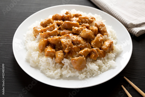 Homemade Orange Chicken with White Rice on a white plate on a black background, side view. Close-up.