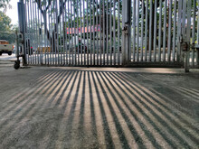 Abstract Background Shadow Line Of Fence Iron Bars On Cement Surface.