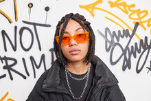 Serious Trendy Hipster Girl Wears Orange Sunglasses Black Jacket And Metal Chains Around Neck Belongs To Youth Subculture Poses Against Graffiti Wall. Millennial People Style Hooliganism Concept