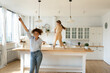 Overjoyed young Caucasian mother and little 8s daughter have fun dancing together in new renovated kitchen. Happy mom and small girl child celebrate moving relocation to own home. Rent concept.
