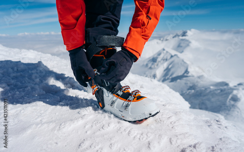 Fototapeta Detailed view on getting ready for skiing, fastening the boots.  The skier wears footwear for skiing and fixes the fastener obraz