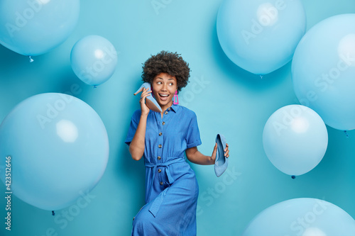 Papel de parede Indoor shot of curly haired young woman dressed in stylish dress holds shoes near ear pretends calling someone poses arounded blue background inflated balloons around