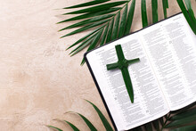 Palm Sunday Concept. Palm Cross On Open Holy Bible And Palm Leaves. Reminder Of Jesus Sacrifice And Christ Resurrection. Easter Passover. Eucharist Concept. Christianity Symbol And Faith
