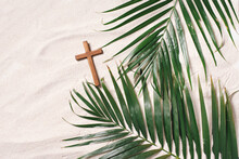 Palm Sunday Concept. Cross Made Of Palm And Tropical Leaves On Sand Background. Christian Moveable Feast To Celebrate Jesus' Triumphal Entrance Into Jerusalem