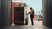 Forklift Driver Loading A Shipping Cargo Container With A Full Pallet With Boxes In Logistics Port Terminal. Latin Female Industrial Supervisor And Safety Inspector With Tablet Managing The Process.