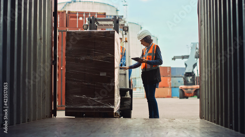Forklift Driver Loading a Shipping Cargo Container with a Full Pallet with Boxes in Logistics Port Terminal. Latin Female Industrial Supervisor and Safety Inspector with Tablet Managing the Process. - fototapety na wymiar