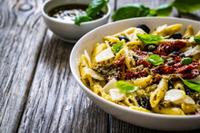 Penne With Basil Pesto, Parmesan, Black Olives And Sun-dried Tomatoes On Wooden Table