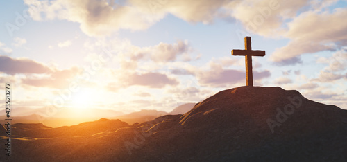 Cross on mountain peak at sunset christian religion