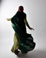 Full Length Portrait Of Red Haired Girl Wearing Celtic, Green Medieval Gown  And Velvet Cloak With Shadowy Backlighting. Standing Pose Isolated Against A Studio Background.