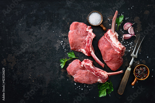 Fototapeta Raw veal Frenched Racks meat with ingredients on rustic dark background obraz