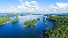 Lakeside Blue Water With Island And Trees In The Distance Blue Sky With White Fluffy Clouds. Tourism In Finland.