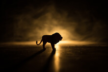 A Silhouette Of Lion Miniature Standing On Wooden Table. Creative Decoration With Colorful Backlight With Fog. Selective Focus